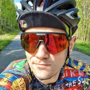 krzysztof jędrzejczyk portret w kasku i dużych okularach kolarskich