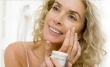 50+ woman applying moisturizer