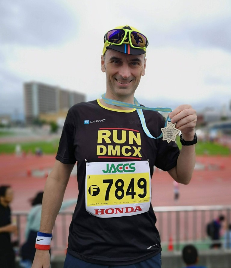 picture of a happy runner holder Hakodate marathon finisher medal