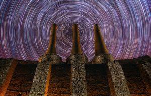 Destacado. Fotografía nocturna de larga exposición. Traza de estrellas startrail circular con 3 chimeneas de una antigua fábrica abandonada
