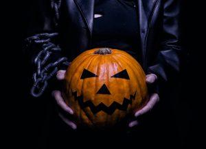 Personaje disfrazado del cuervo sostiene calabaza de Halloween