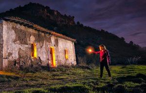 Fotografía nocturna de larga exposición de casa abandonada en las montañas con modelo