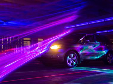 """A car passes through Melanie Clemmons and Zak Loyd's """"Laser Wash"""" in Aurora's Area 3 in the DalPark parking garage in downtown Dallas on Thursday, Oct. 1, 2020."""