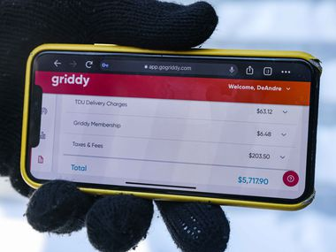 DeAndré Upshaw shows a $5,000 bill from Griddy on his cellphone for his 900-square-foot apartment in Dallas on Friday.