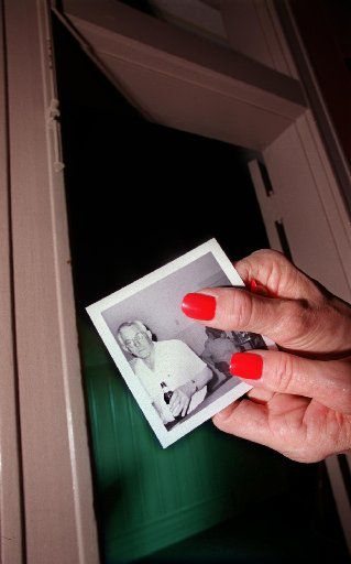 Sons of Hermann Hall manager Jo Nicodemus holds a snapshot of the Hall's former caretaker Louis Barnhardt, who some believe is haunting the place. Nicodemus said she sees phantom figures walking by this doorway frequently.