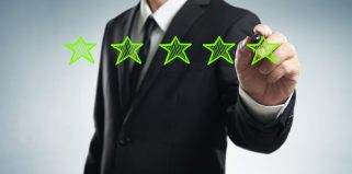 Review, increase rating, performance and classification concept. man draws five green stars to increase rating of his company, blank background.