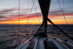 Yacht sailing at sunset during a storm. Luxury vacation at sea
