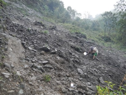 An old woman negotiating a track that had recently been hit by a localised landslide.