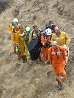 Tired firefighters haul equipment out of a steep valley.