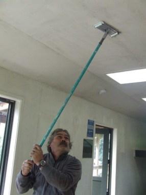 Ranger Mark Tito sanding the hut ceiling.