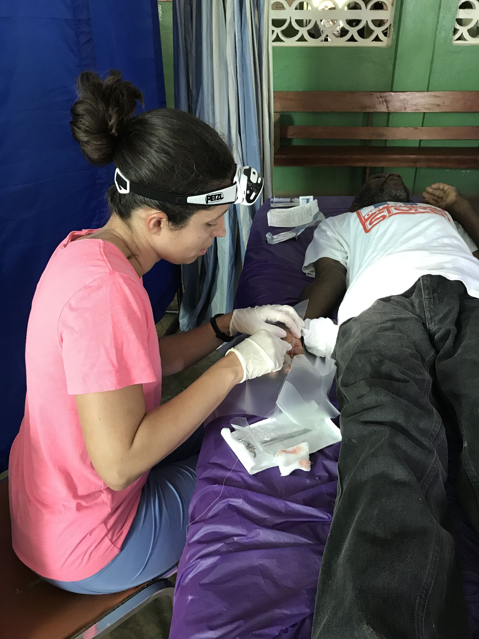 Rachel, a fellow D.O. and Family Practice/ER physician sews up a machete wound.