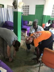 Teaching stretches to a local farmer. Osteopathic principles and practice are free and very useful in a resource poor environment.