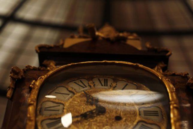 Reloj en el descanso de la escalera y, detrás, un antiguo vitraux.