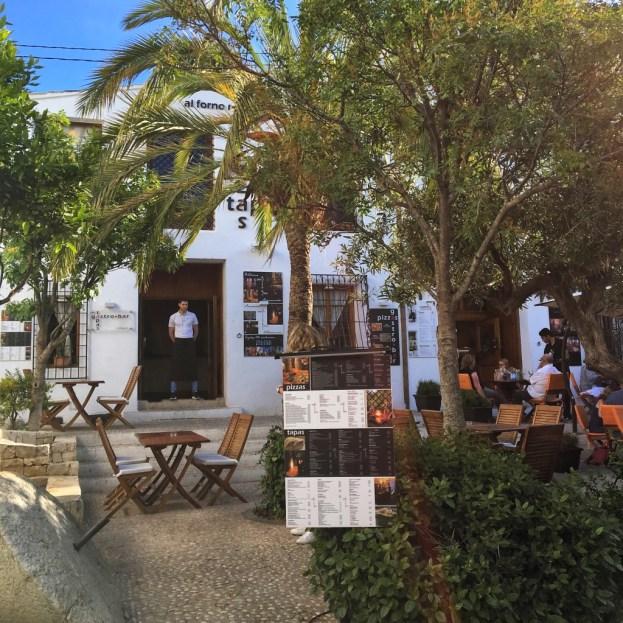 La casa del restaurante y sus mesas, que se distribuyen por la plaza.