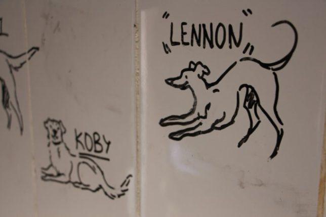 Detalle de los dibujos realizados por estudiantes de Bellas Artes en la pared.