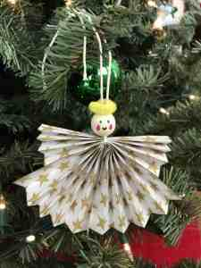 Paper angel ornament hung on a Christmas tree