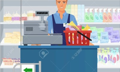 Salesman Man Cashier Standing At Checkout In Supermarket.