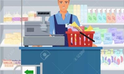 Salesman Man Cashier Standing At Checkout In Supermarket.
