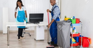 Male And Female Cleaners Cleaning Office