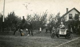 J. E. Walls on horse, Charlie Bowen steering car. 1913 Sports Day at Rouleau.