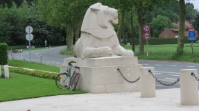 One of two lions standing guard in front of Berks Cemetery Extension near the town of Ploegsteert