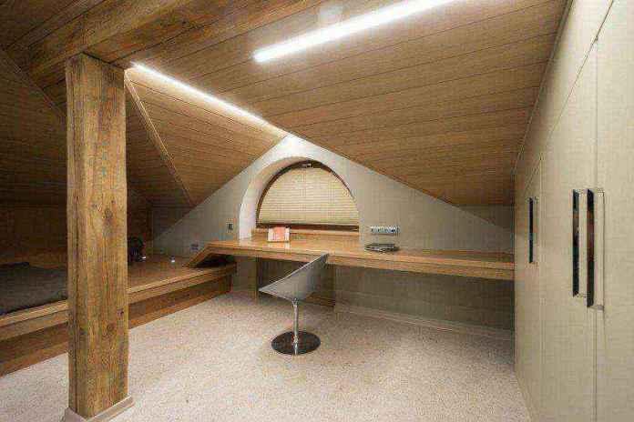 1-2-podium-bed-in-interior-design-teenage-boy-room-attic-floor-sloped-ceiling-asymmetrical-roof-wood-minimalist-style-desk-led-lights-arched-window | Кровати с подиумом в дизайне интерьера: 5 реальных проектов в деталях