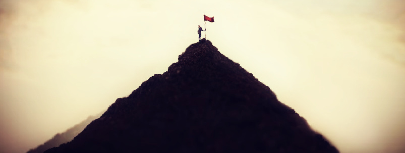woman plants her flag on the mountain peak as a sign of success