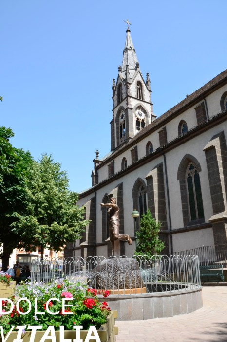 Predazzo fountain and Church of Sts Philip and James