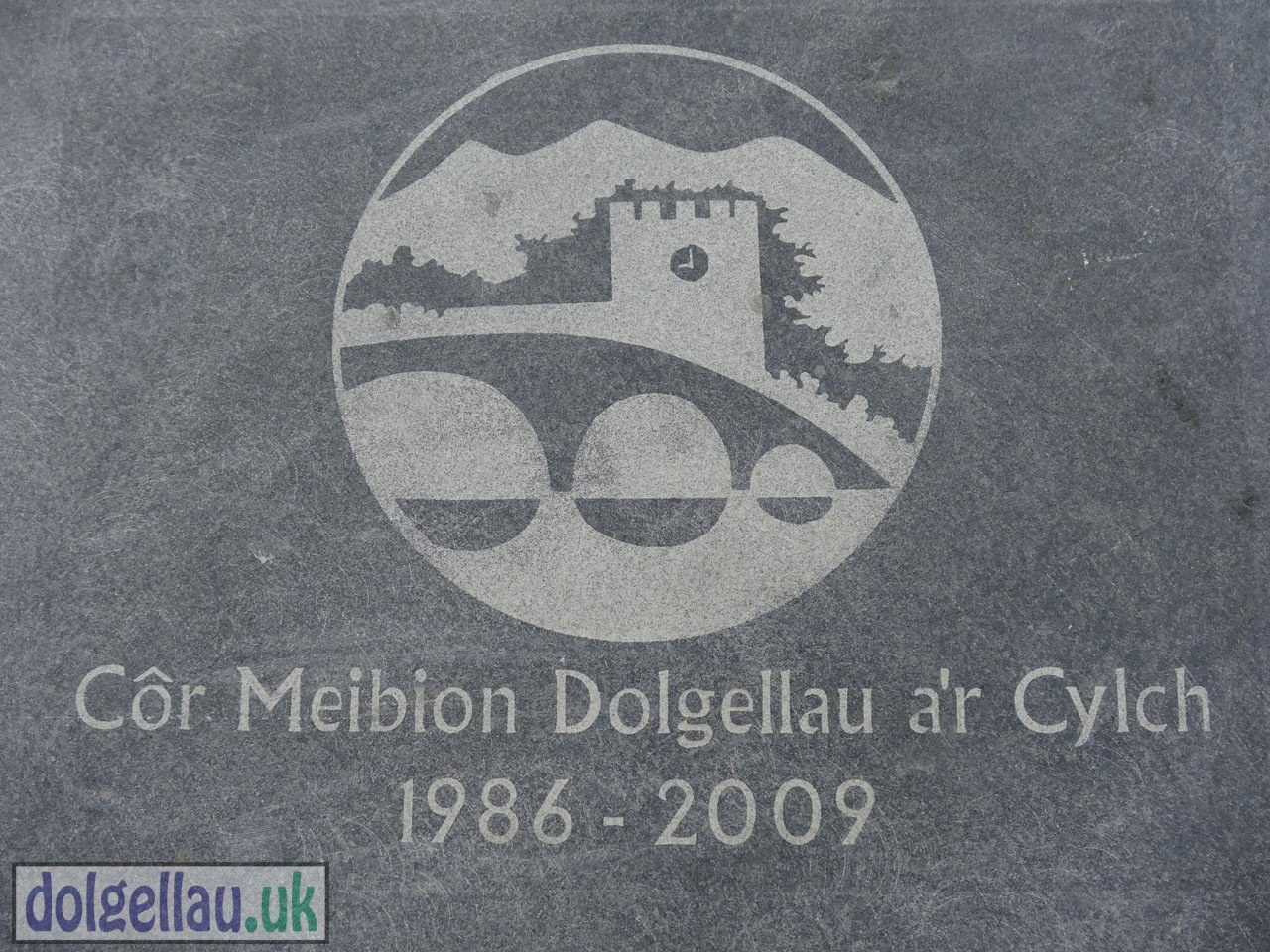 Cor-Meibion Logo Representing The Clock on St. Mary's is at Nine (the town's Curfew Hour in the Past).