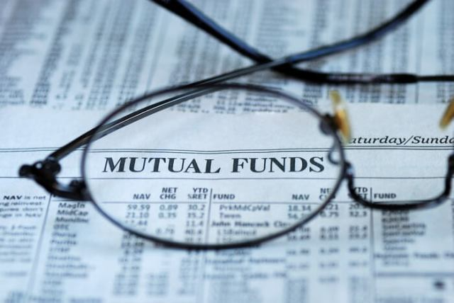 eyeglasses magnifying the mutual funds section in a newspaper