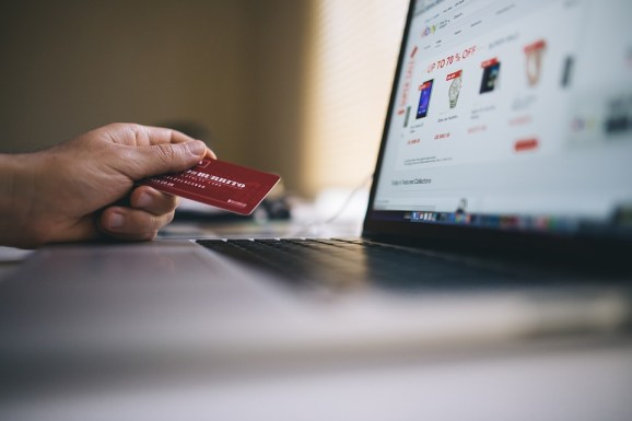 Man Checking his Embrace Home Loans Funds Online while he holds his Bank Card