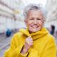Greta Silver grauhaarige Frau lachend mit gelben Mantel