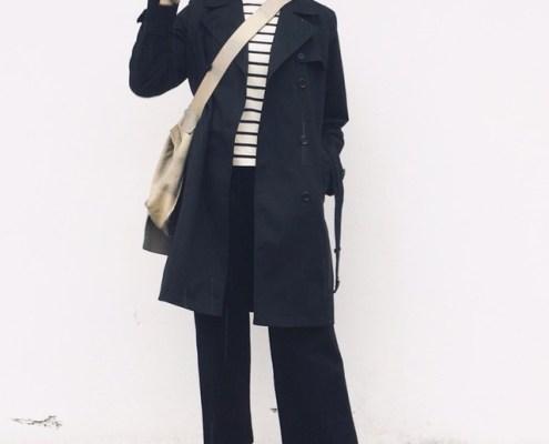 Dolores schwarze Hose schwarzer Mantel Streifenshirt helle Turnschuhe