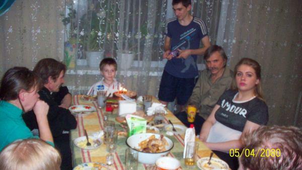 Задувает свечи на торте