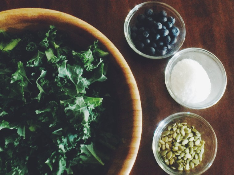 A Whole30 and paleo kale salad with blueberries, pepitas, and coconut.
