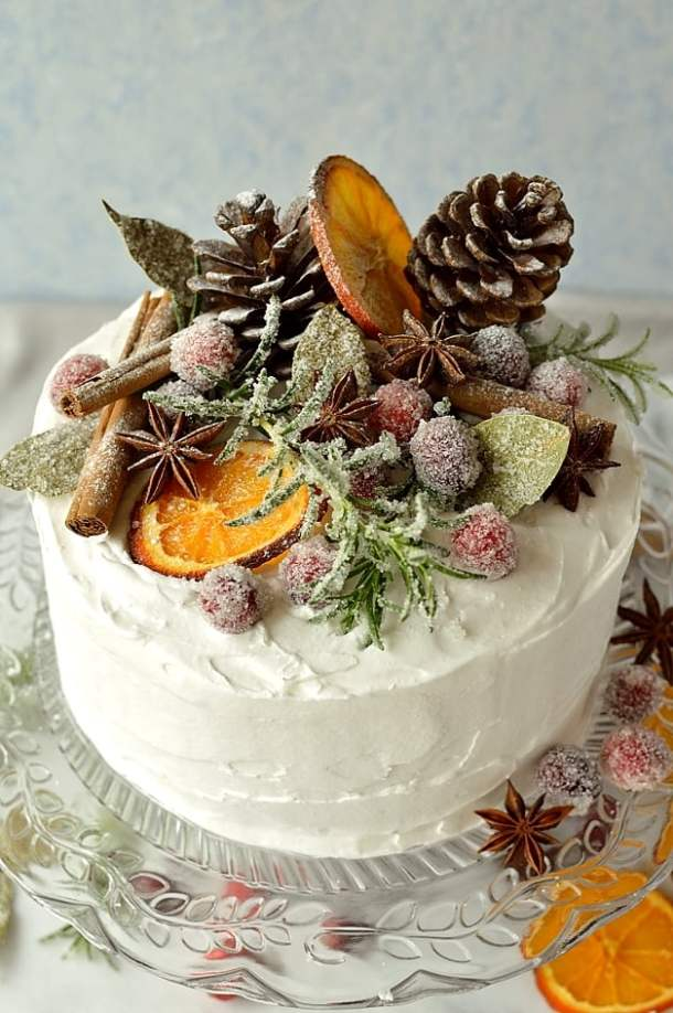 Gingery Christmas fruitcake topped with marzipan, royal icing, sugared cranberries, rosemary and bay leaves, dried orange slices, pine cones and whole spices - Domestic Gothess