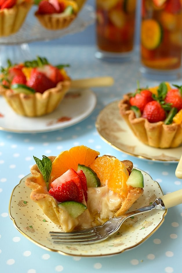 Pimm's cup fruit tarts - citrus shortcrust pastry filled with Pimm's creme patissiere, cucumber & mint jam, strawberries, orange & apple