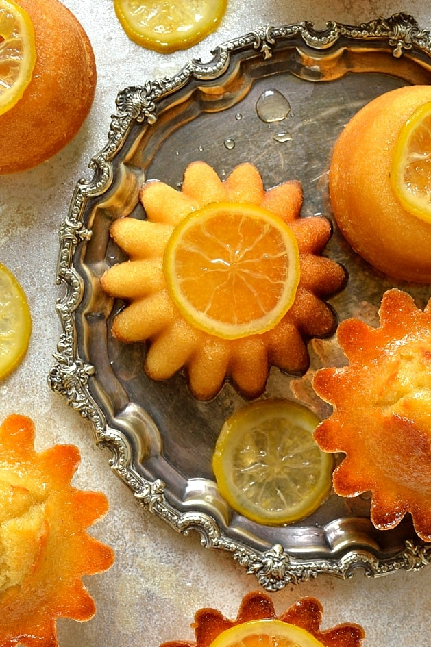 Little syrup coated lemon, olive oil and semolina cakes with candied lemon slices