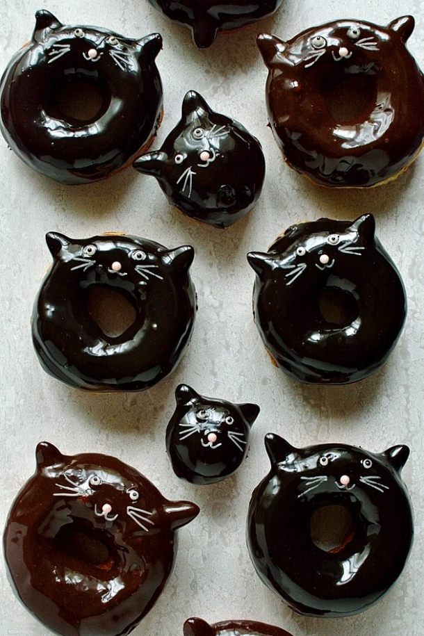 Chocolate glazed fried yeast ring doughnuts with cute cat faces