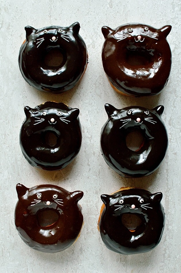 Chocolate glazed fried yeasted ring doughnuts with a cute black cat design, perfect for Halloween!