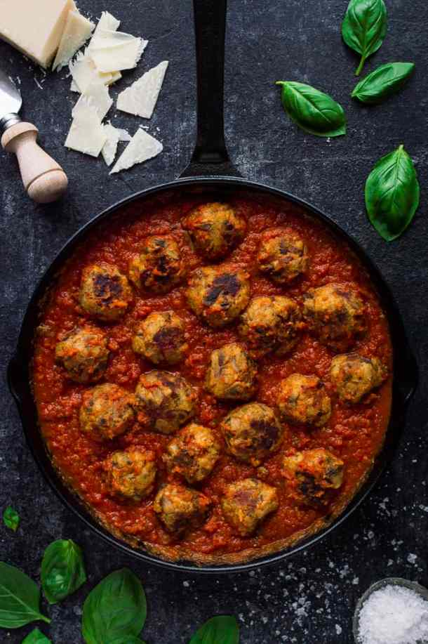 Vegetarian mushroom meatballs with tomato ragu sauce in a black skillet