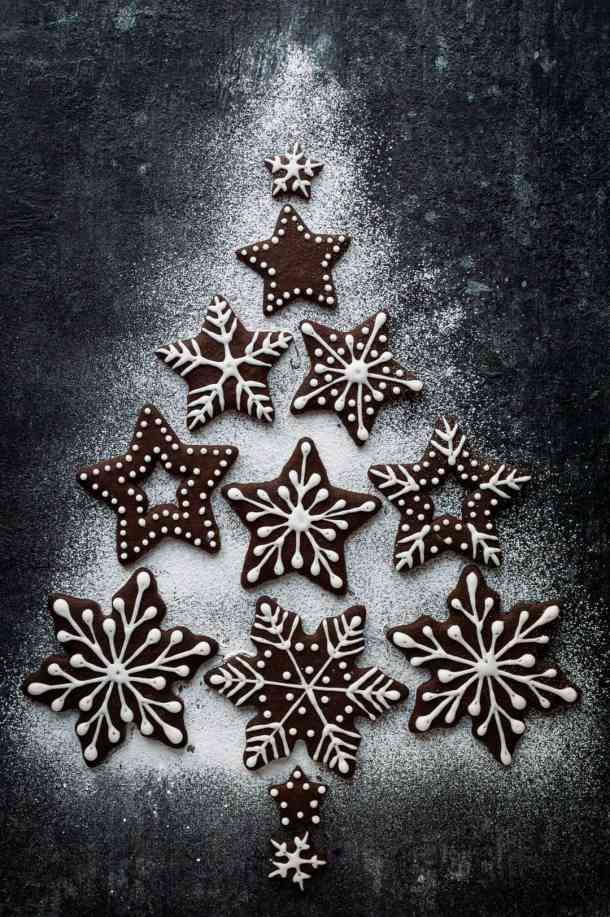 Iced chocolate gingerbread snowflake biscuits arranged into a Christmas tree shape with icing sugar on a dark background.