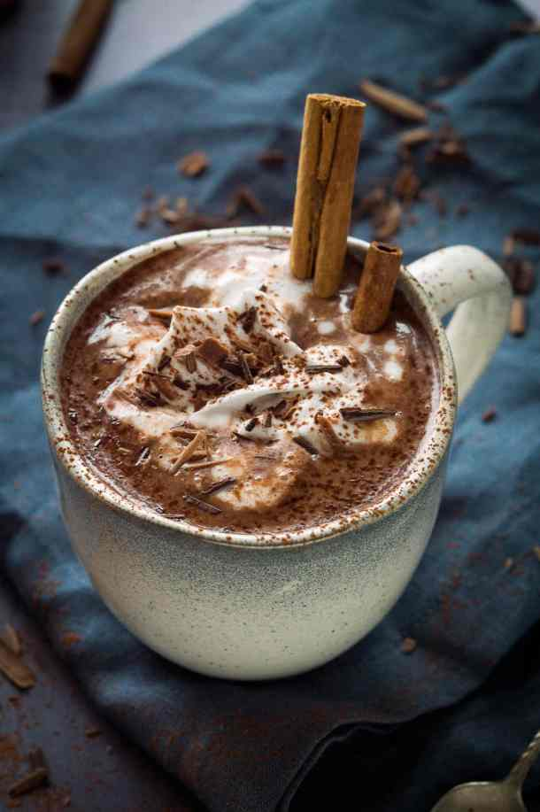Photo of a mug of dairy and refined sugar free rich and creamy vegan hot chocolate in a grey mug topped with coconut whipped cream, chocolate shavings and cinnamon
