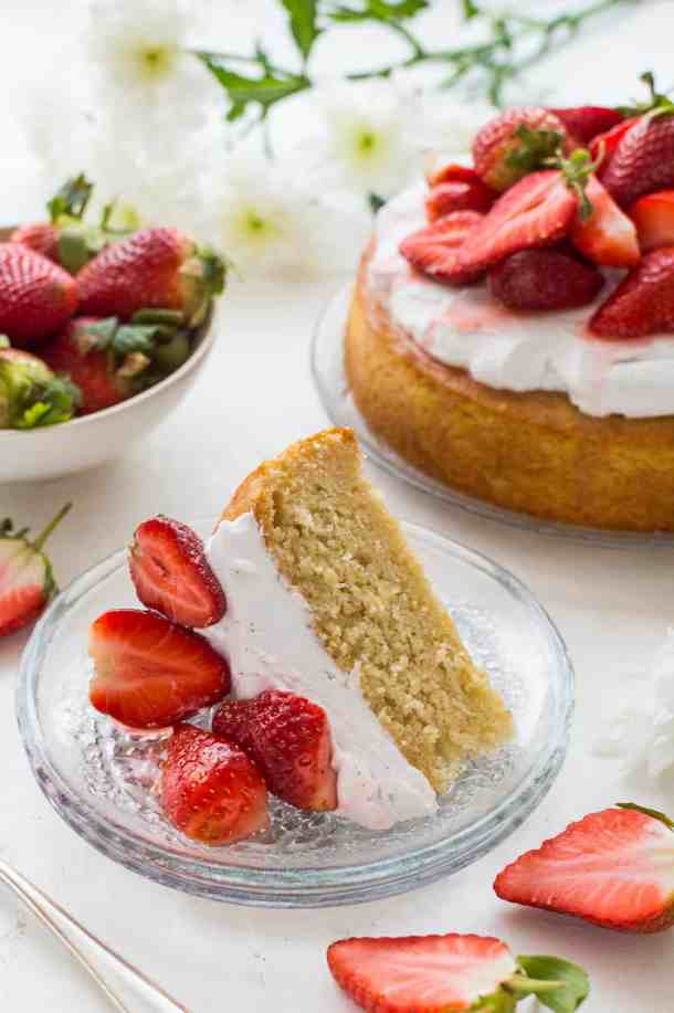 A slice of vegan lemon and almond cake with coconut whipped cream and strawberries.