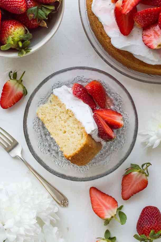 A top down shot of a slice of vegan lemon almond cake on a glass plate with strawberries
