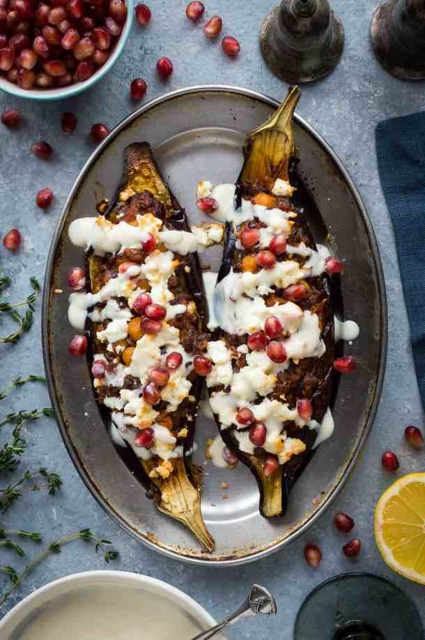 Top down photo of two stuffed eggplants with lemon tahini yogurt sauce and pomegranate.