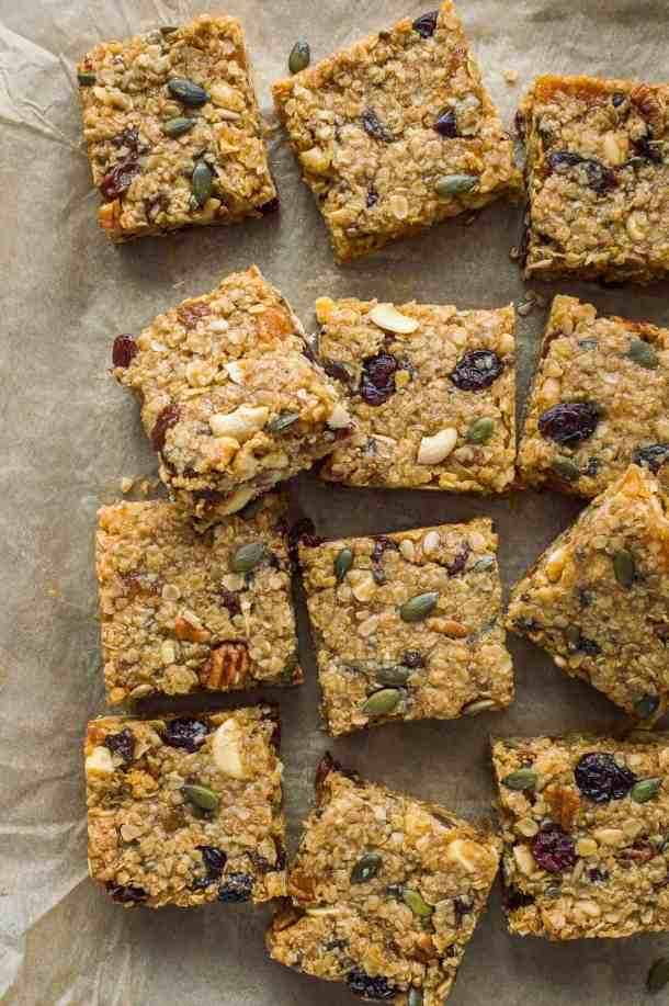 squares of vegan fruit and nut flapjacks on a baking parchment background