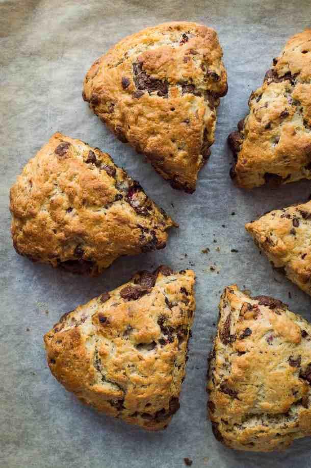 Triangular vegan/dairy free chocolate raspberry scones on a sheet of baking parchment
