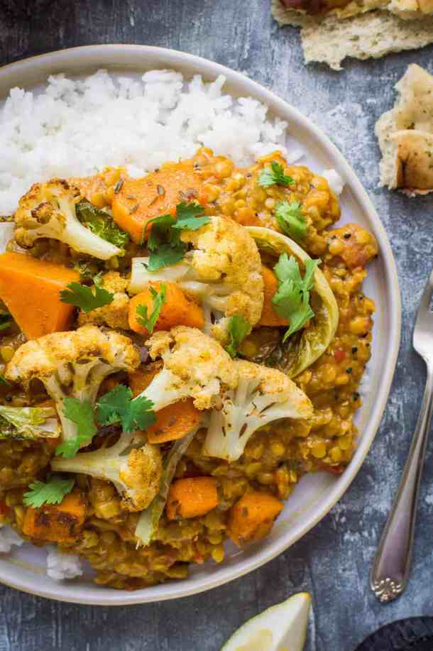 A close up of a plate of vegan red lentil dhal and rice with roasted cauliflower and butternut squash.
