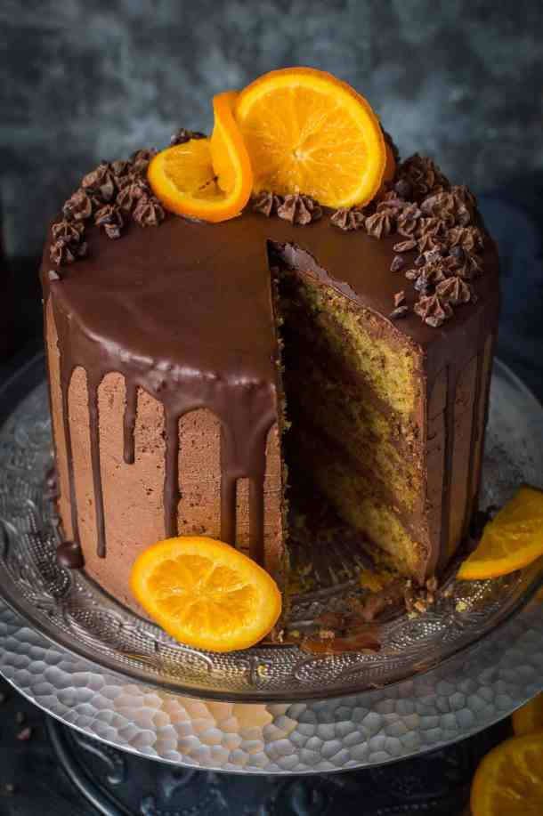 Vegan orange and almond layer cake with chocolate buttercream and candied oranges on a silver cake stand with a slice taken out.